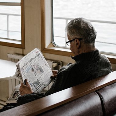 man reading advertisement in newspaper